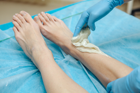 Epilation wax in the spa salon. Beautician imposes wax on womens legs. Close-up.