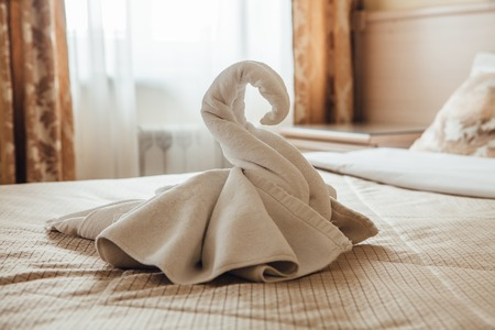 Swan figurine made from towels on a bed in a hotel room. 免版税图像