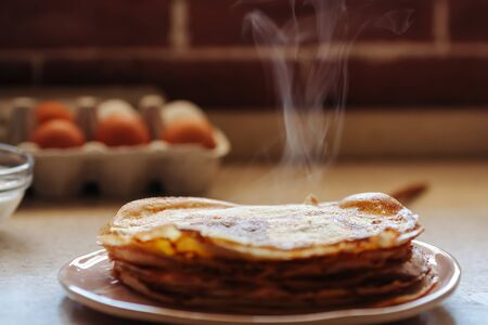 Stack of hot classic Russian thin pancakes. Rustic style. Traditional for the Russian pancake week - Maslenitsa. Close-up. Steam rises from hot pancakes.