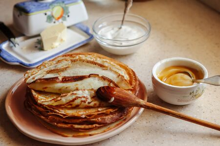 Stack of hot classic Russian thin pancakes. Rustic style. Traditional for the Russian pancake week - Maslenitsa. Sour cream, butter and honey are near the pancakes. Wooden spoon on the pancakes.