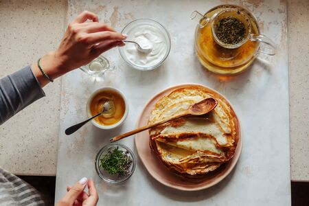 Stack of hot classic Russian thin pancakes. Rustic style. Sour cream, butter, greenery, honey, eggs and tea pot are near the pancakes. Womens hands take a spoonful of sour cream. View from above.
