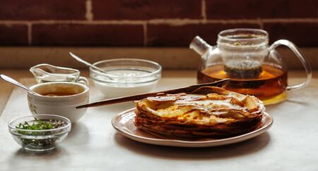Stack of hot classic Russian thin pancakes. Rustic style. Traditional for the Russian pancake week - Maslenitsa. Sour cream, butter, greenery, honey, eggs and tea pot are near the pancakes.