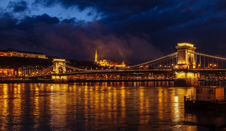 Night View Of Szechenyi Bridge. Famous Chain Bridge Of Budapest. Beautiful lighting and reflection in the Danube River.