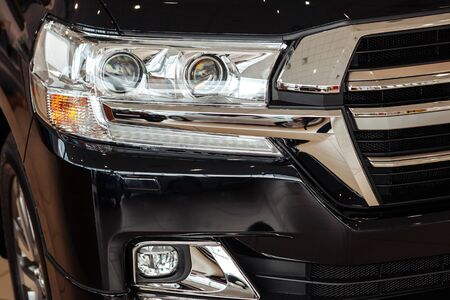 Closeup of a car headlight. Headlight of an expensive new car at a car dealership.