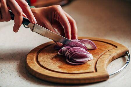 Female hand cuts onion on a cutting board