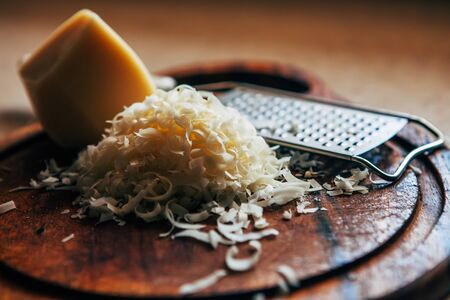 Grated cheese on a cutting board. Next to a piece of cheese and a grater.