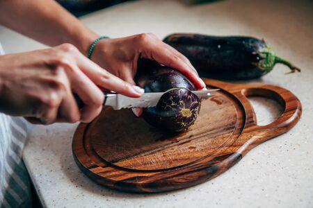 Female hand cuts eggplant on a cutting board