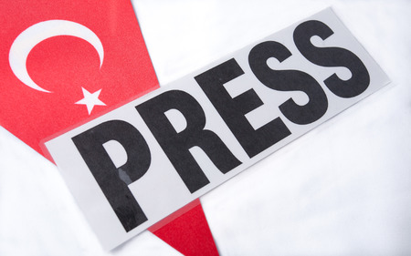 arrests: press panel of journalists lying on the Turkish flag. press freedom in Turkey.