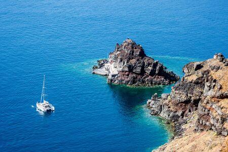 A catamaran anchored off the coast of Santorini, Greece.