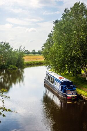 A narrow boat lies moored on the Leeds - Liverpool canal at Halsall, Lancashire, England.