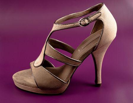 high heeled shoe: Elegant beige high heeled shoe on purple background