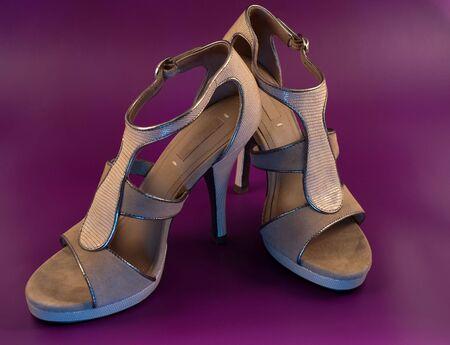 heel strap: Pair of elegant beige high heeled shoes on purple background