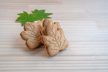 Canadian maple cookies with spring leaves isolated on wooden background.High angle view. canadian food concept Фото со стока