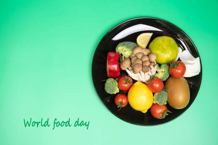 World food day, vegetarian day or healthy food concept. Fresh vegetables and fruits on black plate on green background. Top view