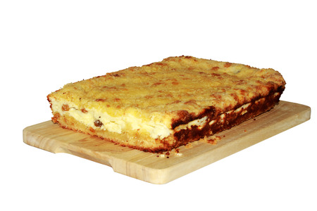 Newly-baked cottage cheese casserole in a dish on a wooden chopping board