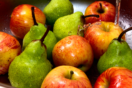 warm water: Wash apples in a sink under running warm water. Stock Photo