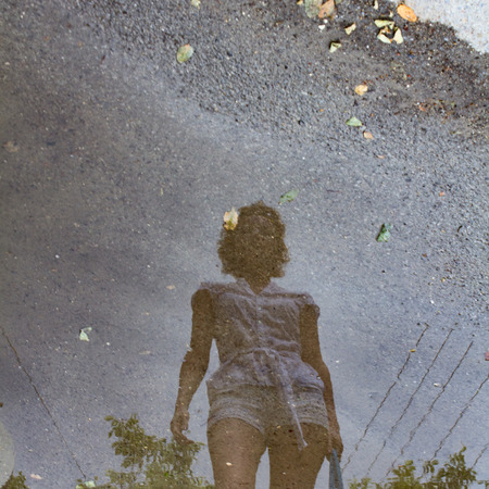 walking zone: a reflection of a young girl in a puddle after rain.
