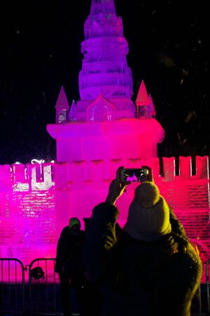 ice sculpture: 01062016 Russia. Moscow, Poklonnaya Gora, Victory Park. The exhibition of ice sculptures Ice Moscow. In the family circle. Girl photographs ice sculpture of the Moscow Kremlin Spasskaya Tower