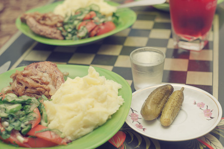 Salt cucumbers, potato, fried meat, salad from fresh cucumbers and tomatoes. Very delicious food on the plate.