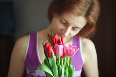 Bunch of tulips in woman hands. The holiday of spring and love. International Women's Day on 8 March. Standard-Bild