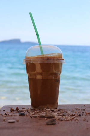 frappe: Ice frappe in plastic cup on the beach Stock Photo
