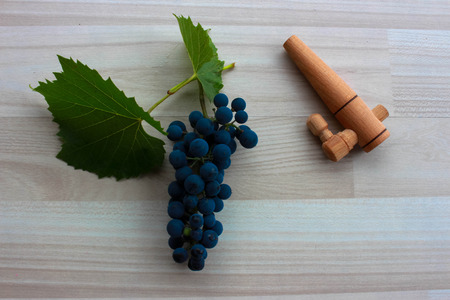 spigot: Blue grapes and wooden spigot on beige floor