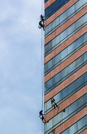 group of workers cleaning windows service on high rise building Zdjęcie Seryjne