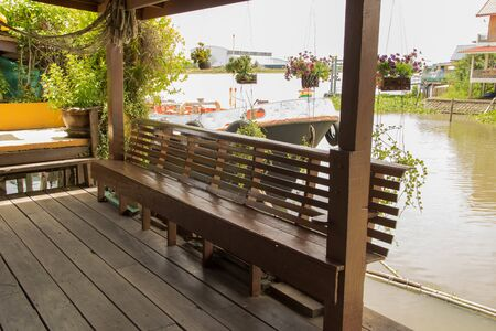 The wooden long chair beside the canal. Armchair made by wood decorate at the side of canal.
