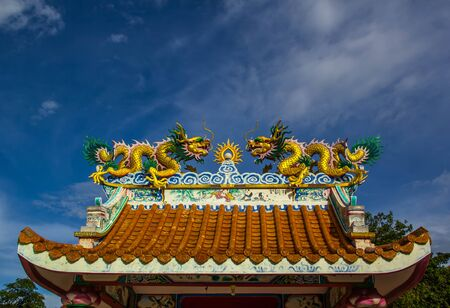 Chinese dragon statue on the roof with a sky blue background