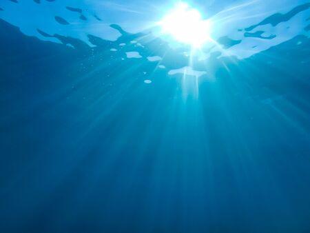 abstrakter Unterwasserhintergrund mit Sonnenstrahl und Wasserwellen