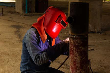 Welder erecting technical steel in construction site Stock fotó