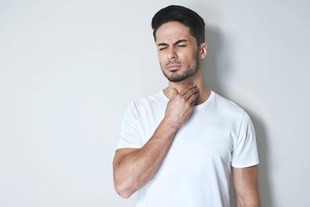 Junger Mann, der Halsschmerzen hat und seinen Hals berührt und trägt ein loses weißes T-Shirt gegen hellgrauen Hintergrund. Schwer zu schlucken