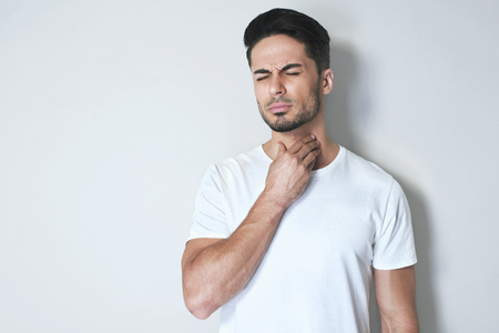 Young man having sore throat and touching his neck, wearing a loose white t-shirt against light grey background. Hard to swallow Stock Photo