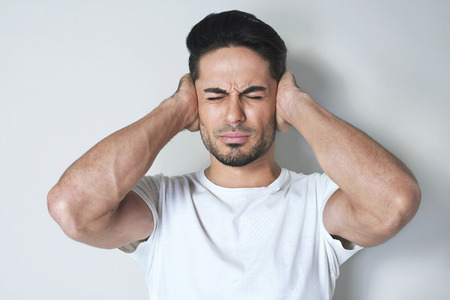Keep silence! Stressed man covers his ears with hands, dressed in causal white t-shirt against grey background Stock Photo