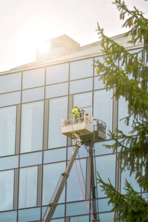 A worker in overalls on an elevator washes the glass wall of a building. Фото со стока