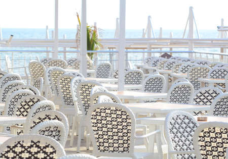 White plastic furniture in a cafe on the coast before the start of the beach season.