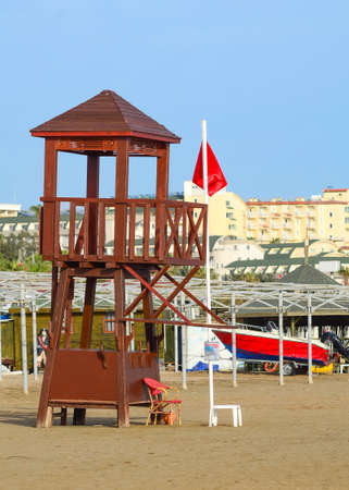 Lifeguard tower on an empty beach with a red flag raised. A sign prohibiting swimming in a sea.