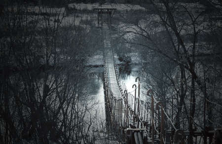 Creepy dark old suspension bridge across the river in the fog. Background for halloween. Banque d'images