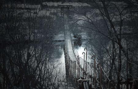 Creepy dark old suspension bridge across the river in the fog. Background for halloween.