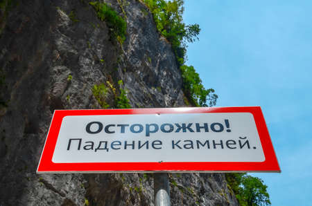 Warning sign in the mountains about the rockfall. Translation from Russian: Caution Falling stones.