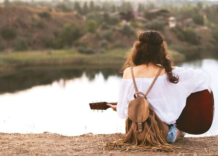 girl in boho style sits on a lake background with a guitar in hand