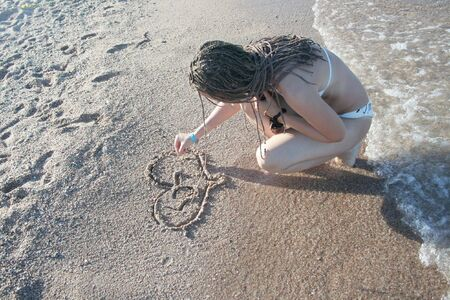 The girl draws on sand photo