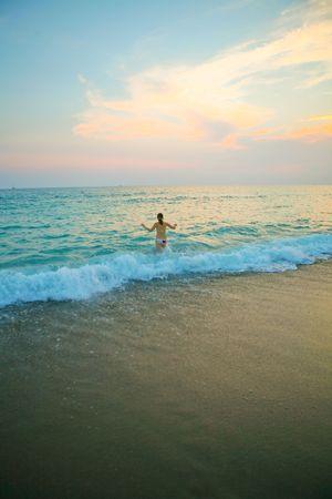 Beautiufl girl in a white bikini running into the ocean photo