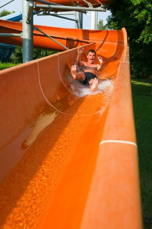 Man riding down a water slide Stock Photo