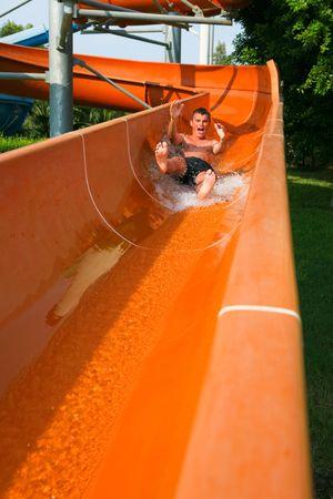 Man riding down a water slide Фото со стока