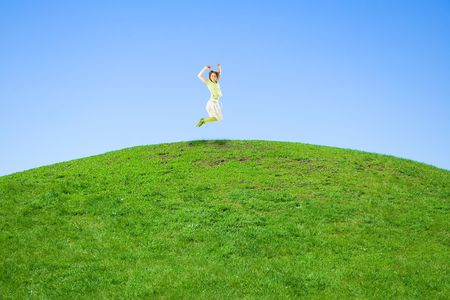 woman jumping on a green meadow photo