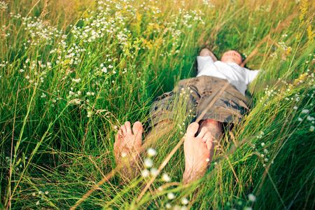 flowers boy: young adult man in spring grass