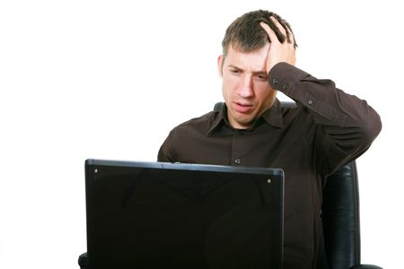 Businessman with laptop, holding head in hands photo