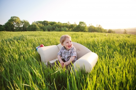 Little adorable boy sits in the chair in the grass photo