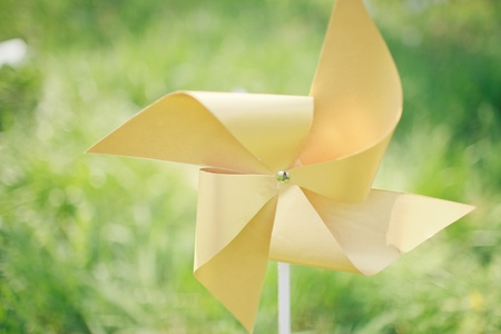 paper windmill in green grass field photo